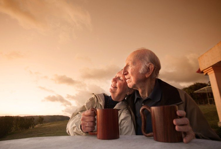old couple holding mugs, outside at sunset