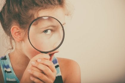 Little girl looking through magnifying glass.